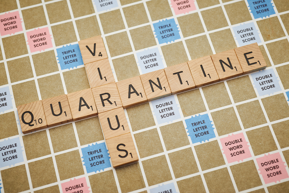 scrabble board with virus and quarantine spelled out