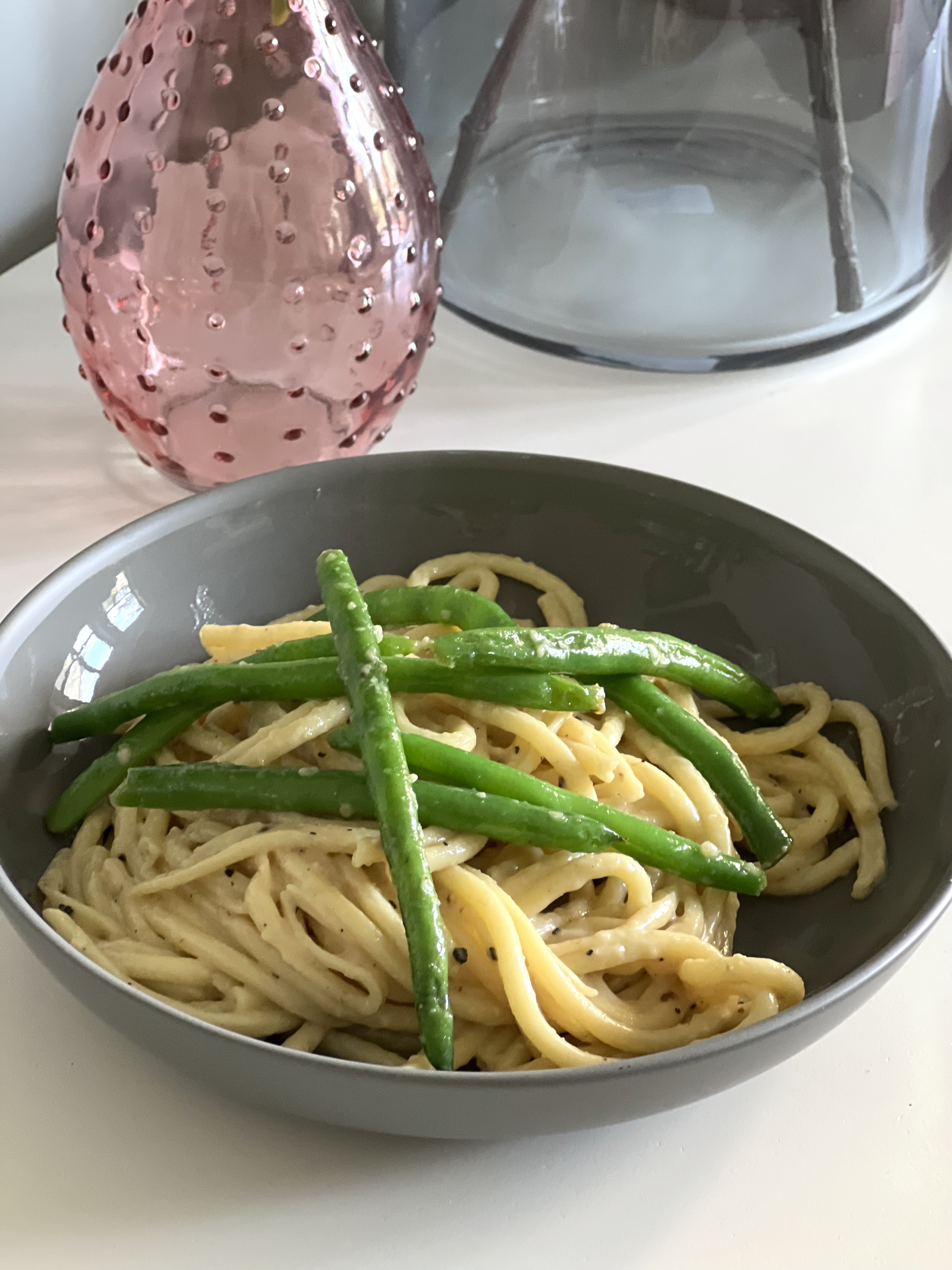 bowl of bucatini with creamy, vegan sauce and topped with green beans.